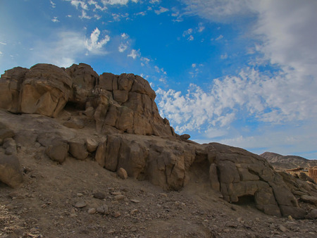 rounded edges: Rounded edges of the rocks in the egyptian desert. Blue sky with intense white clouds. Stock Photo