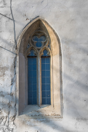 gothic window: Original gothic window with a stone frame and a glass reflecting the sky. Church of Saint Cross in Devin, Bratislava, Slovakia.