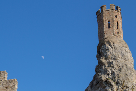 morava: Part of ruins of castle Devin in Slovakia.  Maiden tower, built on the edge of a high rock. Bright blue sky with moon.