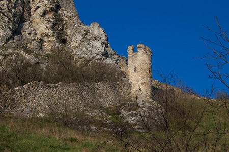 surrounding wall: Ruins of the former famous fortress, Devin castle, Bratislava, Slovakia. Surrounding wall with a tower. Bright blue sky.