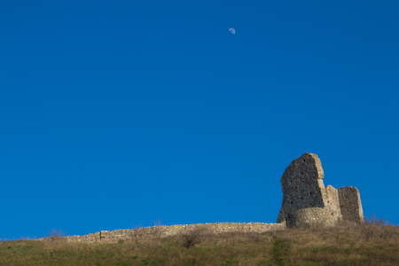 surrounding wall: Part of the former fortress, ruins of the Devin castle, Bratislava, Slovakia. Surrounding wall and a building on the hill. Bright blue sky with a moon. Editorial