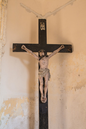 crucified: Wooden cross with crucified Jesus Christ in the entrance to the church. Enlightened by sunlight.
