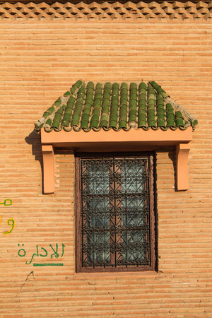 small roof: Closed window with an ornamental lattice and with a small roof with green tiles. Wall made of small bricks. Stock Photo