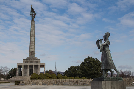 liberating: Memorial for the soldiers, who perished while liberating Bratislava during the World War II. Statue of two girls, welcoming the liberators. Blue cloudy sky.