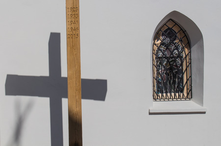 gothic window: Wooden cross with a years of Saint Missions and its shadow on the wall of the gothic church in Svaty Jur, Slovakia. Traditional gothic window beside. Stock Photo