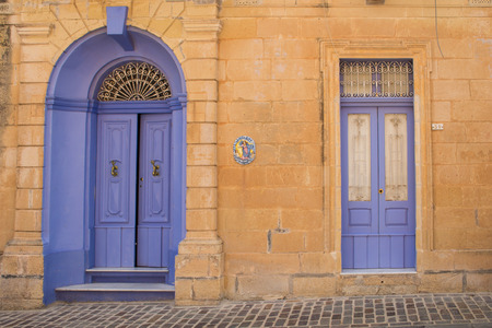 well made: Well preserved house made of stones with small and big doors painted unusual violet color. Small city Had-Dingli at the mediterranean island Malta. Stock Photo