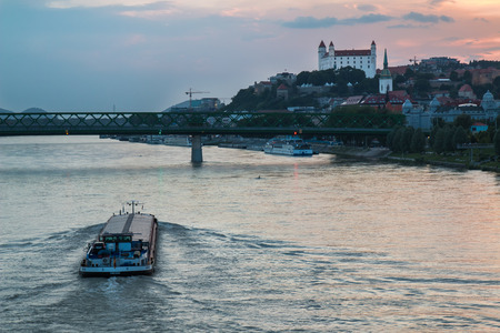 presidency: River Danube crossing the city Bratislava in the light of the sunset. View on the old city with the historical cathedral and the castle on the the hill.