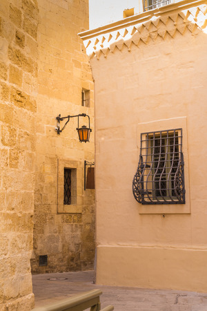 baroque architecture: Fusion of arabian and baroque architecture in the former capital of island Malta - Mdina, medieval fortress. Stone houses , yellow color in the sunlight. Stock Photo