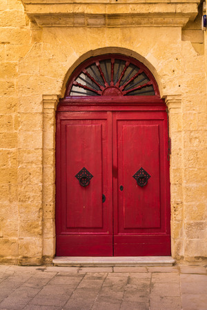 baroque architecture: Former capital of island Malta, fusion of arabian and baroque architecture. Wall of a house made of stones with a ornate red door.