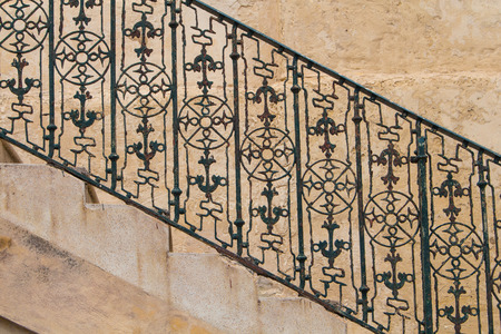 metal handrail: Part of the stairs from a side, with visible rhythm of the steps and iron handrail with motive of compass and anchor. Stone wall in the background. Island Malta