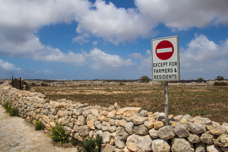 no entrance: Fence made of stones lining a field. No entrance sign. Blue sky with intense white clouds. Mediterranean island Malta.