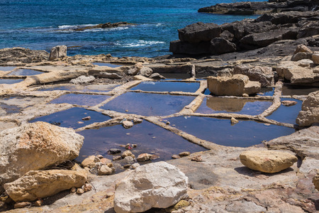 evaporation: Holes in rocks at the seaside of the Mediterranean sea, for evaporation the water and getting sea salt. City Marsaskala, island Malta.