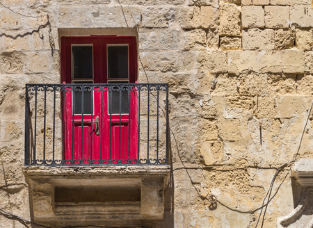 balcony door: Old traditional building made of stone bricks with a balcony and a red door. Valletta, capital of island Malta.