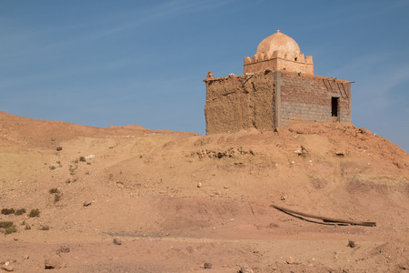 Old and not finished construction of a mosque on hill beside the road to the city Ait Ben Haddou. Dome without a tower. Bright blue sky. Orange sandy soil. Stock Photo