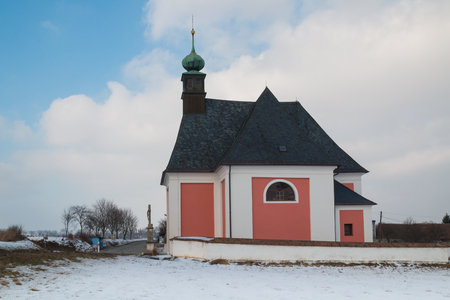 Christian church in village Kninice in Moravia, Czech republic. Snow on the field. Intense cloudy sky. Green tower of the church. Stock Photo