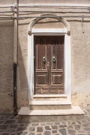 Entrance of a house with old traditional wooden gates with two green knockers. Wall partly in the light and partly in a shadow. Street of Castelsardo, Sardinia, Italy.