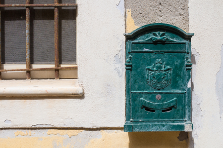 Wall of a house with a part of grated window and old green mailbox. Corner of a letter in the mailbox slot. Castelsardo, Sardinia, Italy. Foto de archivo