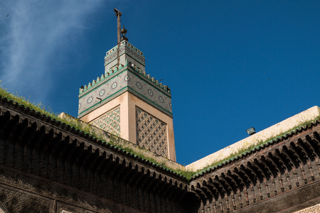 View from the yard of the islamic school Madrasa Bou Inania, Fez, Morocco. Details of the architecture and tower of the mosque. Blue sky, white cloud.