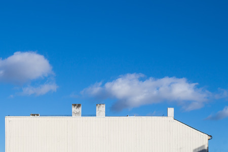 Structured white side of a house. Several chimneys. Bright blue sky with several clouds.