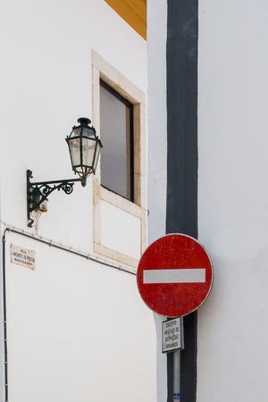 White wall of the buildings. Grey line and a no entry traffic sign in the foreground. Traditional lantern and a window in the background. Lagos, Algarve, Portugal. Banque d'images