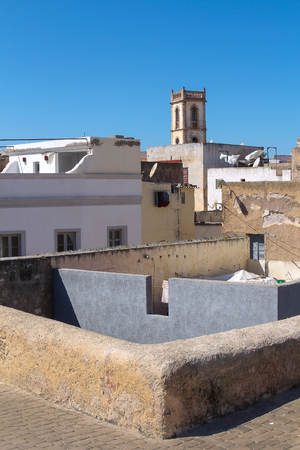 Skyline of the old city in the former portuguese fortress. Tower of a hotel built in traditional portuguese style. El Jadida, Morocco. Bright blue sky.