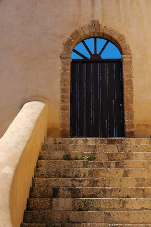 Stone stairs to the wooden gate with an arch. Arch with holes, where is visible bright blue sky. Building in former portuguese fortress in El Jadida, Morocco.