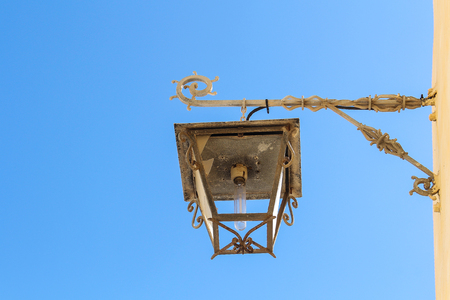 Lantern hanging on the yellow color of the facade of a house. White ornate hanger. Broken glass of the lantern. Modern bulb. Bright blue sky. El Jadida, Morocco.