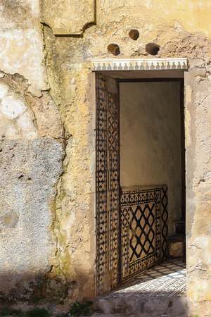 Yellow peeled off facade of an old house. Opened door. Entrance, wall and floor decored by traditional ceramics tiles. El Jadida, Morocco.