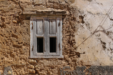 Peeled off facade of an old house. Window with a shutter made of natural wood, partly broken. El Jadida, Morocco.