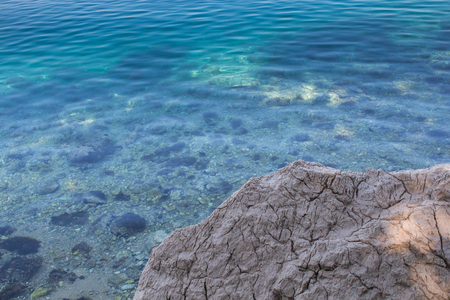 Rock with cracks on the coast of Adriatic sea. Turquoise color of the sea water in the distance. Thanks to the clean and clear water visible stones on the bottom. Omisalj, island Krk, Croatia. Stock Photo