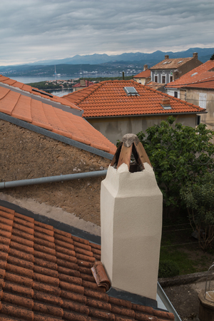 Orange roofs of the old houses, built on a hill. View on the bay of Adriatic sea. Mountains of the background. Intense spring clouds. City Omisalj, island Krk, Croatia. 写真素材