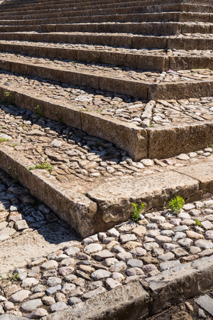 Structure of the stairs made of stone outdoors, including their corner. Little plants among the stones. Sunny day. Estoi, Portugal. 版權商用圖片