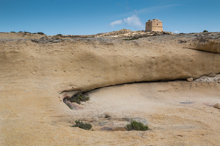 Dry rocky and sandy country with a historical Dwejra tower at island Gozo, Malta. Blue sky. 免版税图像