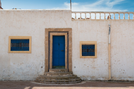 Street with a house with bright blue door and window grids and white color of the facade. Rounded stairs.  Terrace on the roof. Blue sky with white clouds. Street in Kasbah de Oudaias, Rabat, Morocco.