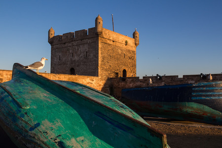 Wooden fishing boats in a port. Tower of the fortification in the bacground. Blue morning sky. Essaouira, Morocco. Redakční