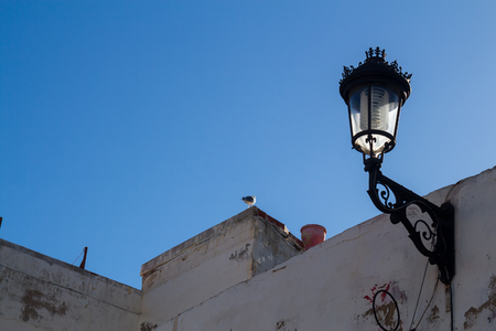 Classic shape of a street lamp - lantern, as an european heritage on a building in Safi, Morocco. Enlightened by a morning sunlight. Bright blue sky.