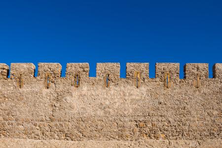 Detai of the stone wall of the former historical portuguese fortress (castle) Dar el Bahar. Bright blue sky. Safi, Morocco. Banco de Imagens