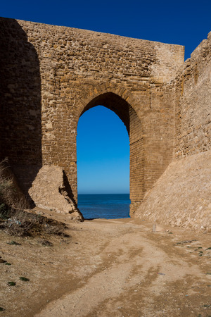 Stone walls of the ancient portuguese fortress (castle) Dar el Bahar with an arc gate. Located on the coast of Atlantic ocean in Safi, Morocco. Bright blue sky.