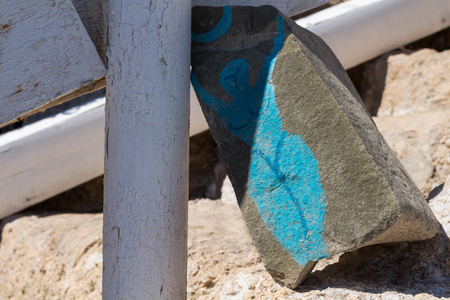 Piece of broken stone brick with a blue painting of a naked lady. Matala, Crete, Greece. Stock Photo