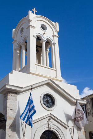 White facade of the church with a high tower with belfry. Orthodox church of Our Lady of the Angels. Greek flag blowing in the wind. Blue sky with white clouds. Rethymno, Crete, Greece.