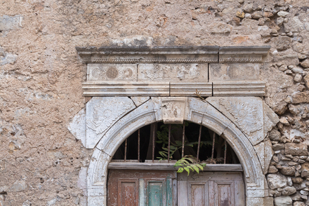 Ornate stone frame of the door of an abandoned house with stone walls. Part of a wooden closed door. Grille with leaves of a wild plant. Street in Rethymno, Crete, Greece.