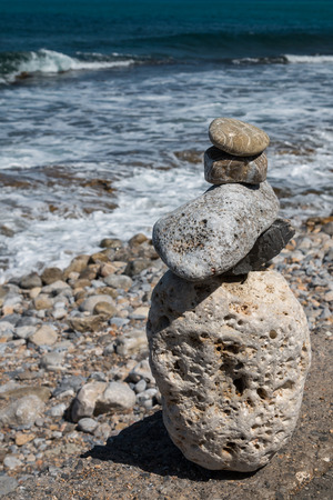 Various sizes of the pebbles, used for the meditation pyramid. Water of the mediterranean sea in the background. Gouves, Crete, Greece.