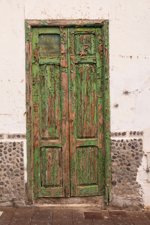 Characteristic green color of the details and gates of the houses. Old peeled of color, creating a texture. White facade of the house. Arico Nuevo, Tenerife, Canary Islands, Spain.