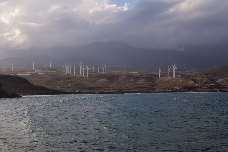 View from the coast on the Atlantic ocean waves. Wind electricity power stations, city and a mountain in the background. Cloudy sky. Punta de Abona, Tenerife, Canary Islands, Spain.