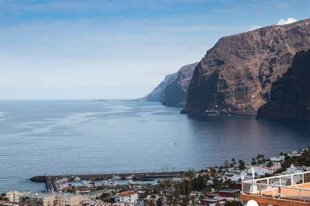 Los Gigantes cliffs in the surroundings of Puerto de Santiago, city in the west of the island. Calm water of Atlantic ocean.  Blue sky with light clouds. Tenerife, Canary Islands, Spain.