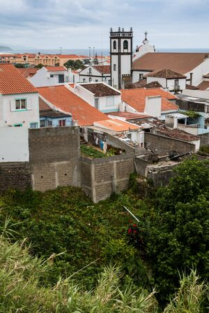 Roofs, mostly with bright orange tiles and a belfry tower of a church with traditional white facade and brown details. Cloudy sky. Maia, Sao Miguel, Azores Islands, Portugal. Stock fotó
