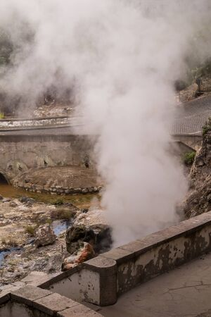 Steam from the hot volcanic springs in the thermal park, jetting among the stones. Furnas, Sao Miguel, Azores Islands, Portugal. Stock Photo