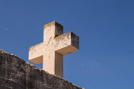 Wall and a heavy cross made of stone. Summer blue sky in the background. Primosten, Croatia.
