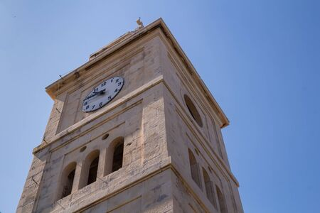 Building of church of Saint George, made of stone. Tower with belfry and clock. Summer blue sky. Primosten, Croatia. Stock Photo