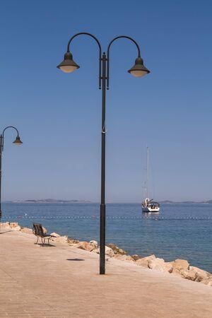 Street lamps on the promenade beside the bay of Adriatic sea. Blue summer sky. Primosten, Dalmatia, Croatia.